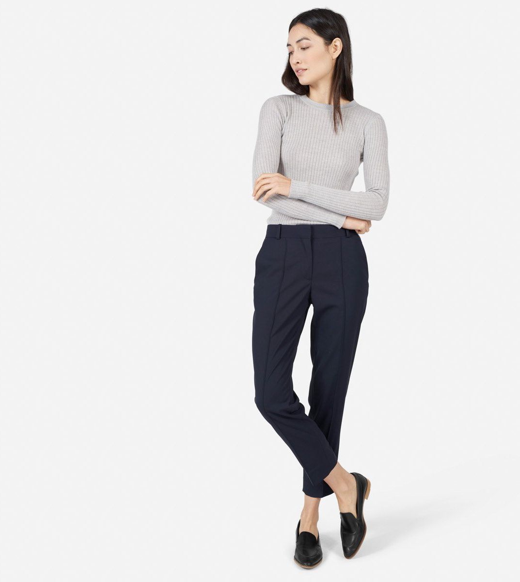 eae756d934d A model wearing Everlane s cropped navy trousers and a gray sweater