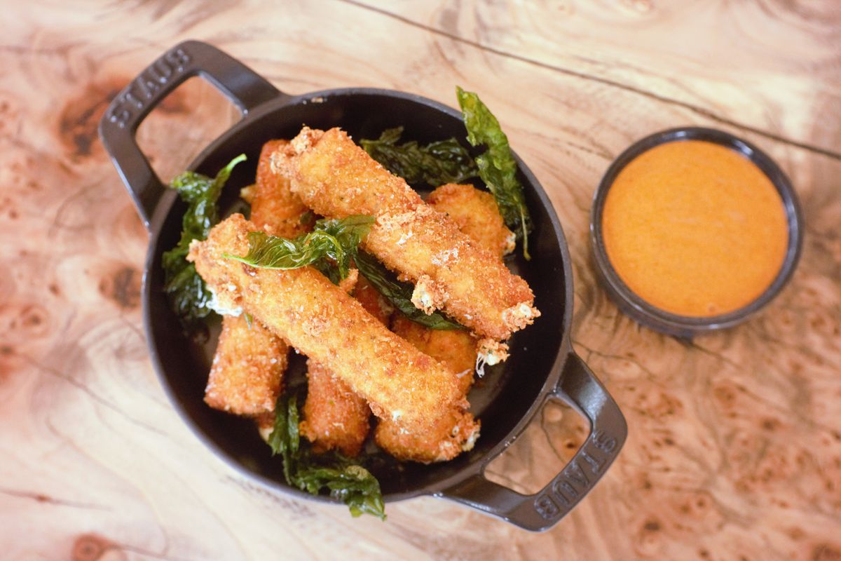 An overhead photograph of a small cast iron skillet filled with several mozzarella sticks