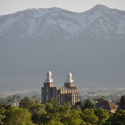 The Logan LDS Temple and Wellsville Mountains are seen from Old Main.