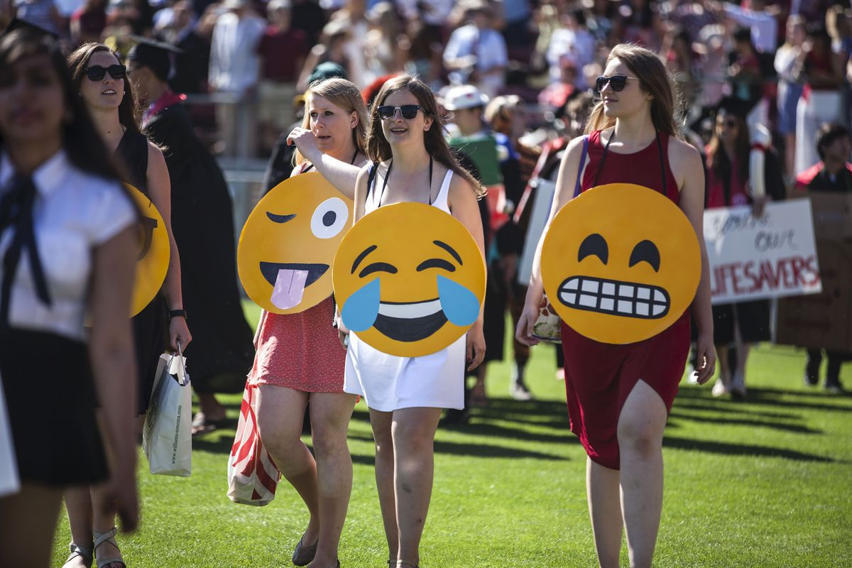 Three young women wear emoji face placards as they walk through a college crowd.
