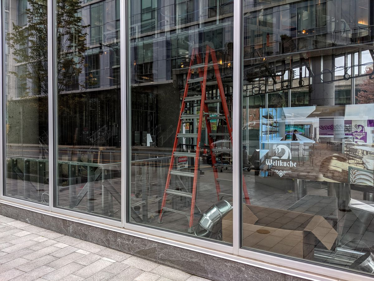 Renderings in the window of an under-construction site that will be home to a restaurant