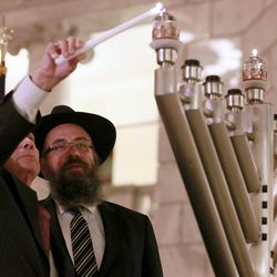 Rabbi Benny Zippel watches as Ambassador John Price lights the candle for the Menorah Lighting Ceremony in the state Capitol Tuesday, Dec. 16, 2014, in Salt Lake City.