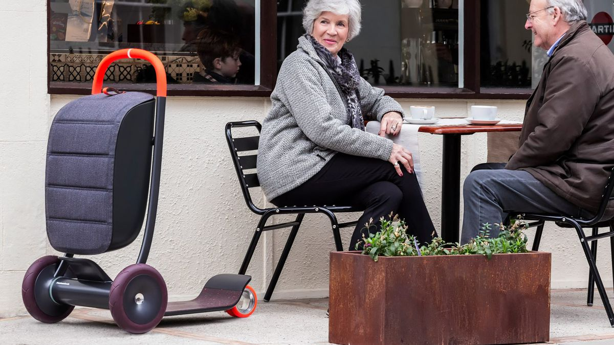 A scooter with storage compartment in the front standing next to an elderly couple sitting outside at a cafe.