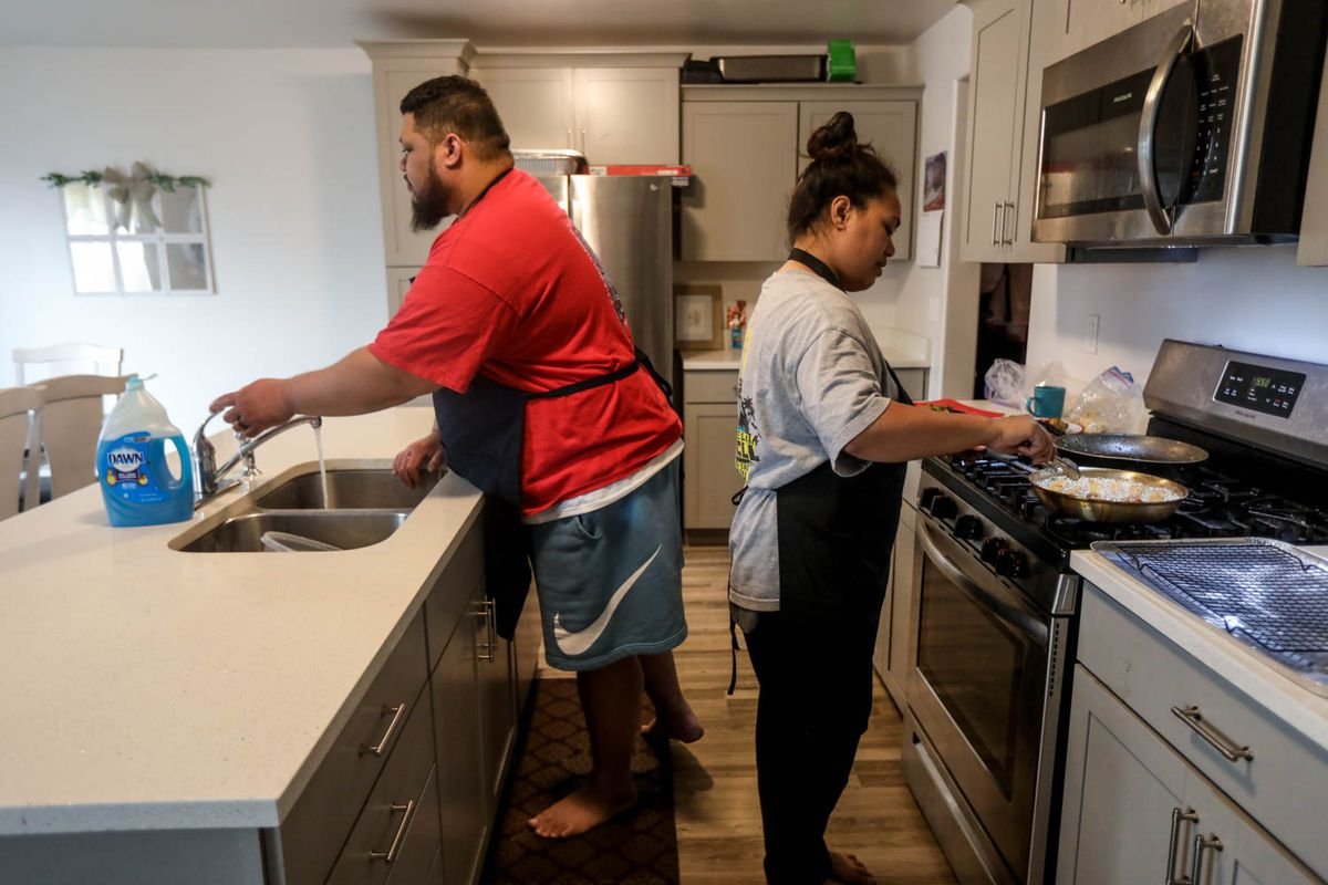 Nathan Savaiinaea, left and Lola Savaiinaea, right, owners of Sawrap, a microenterprise home kitchen, prepare food to sell in Provo on Thursday, Feb. 18, 2021.