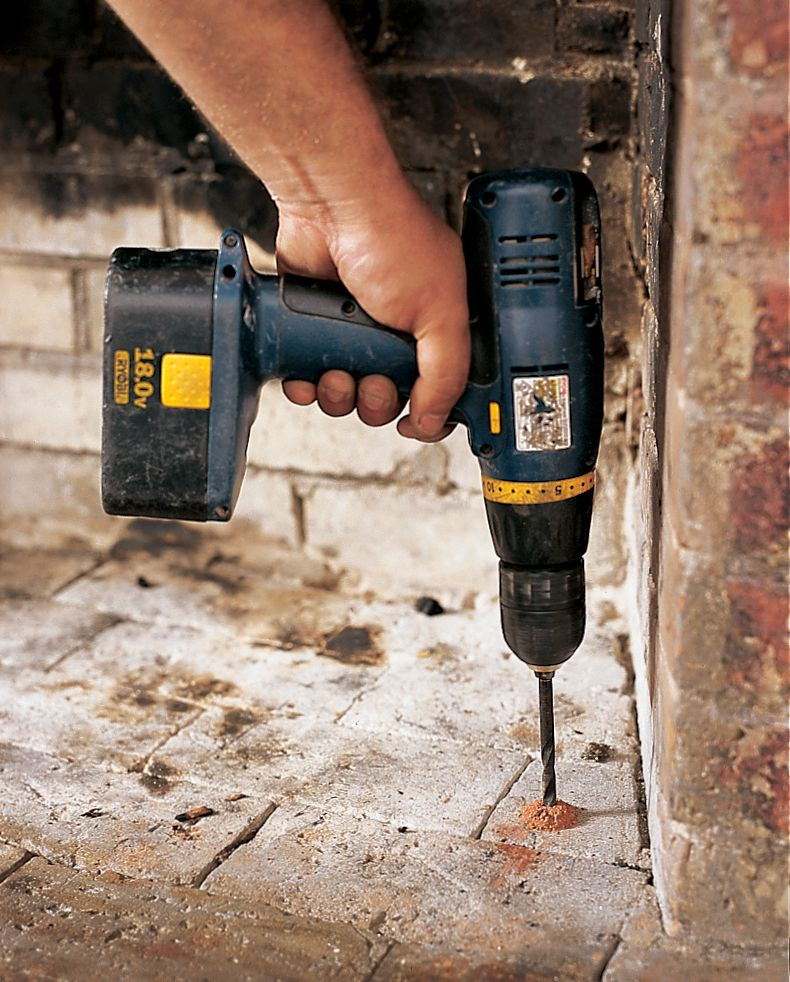 Person drilling a hole in brick floor.
