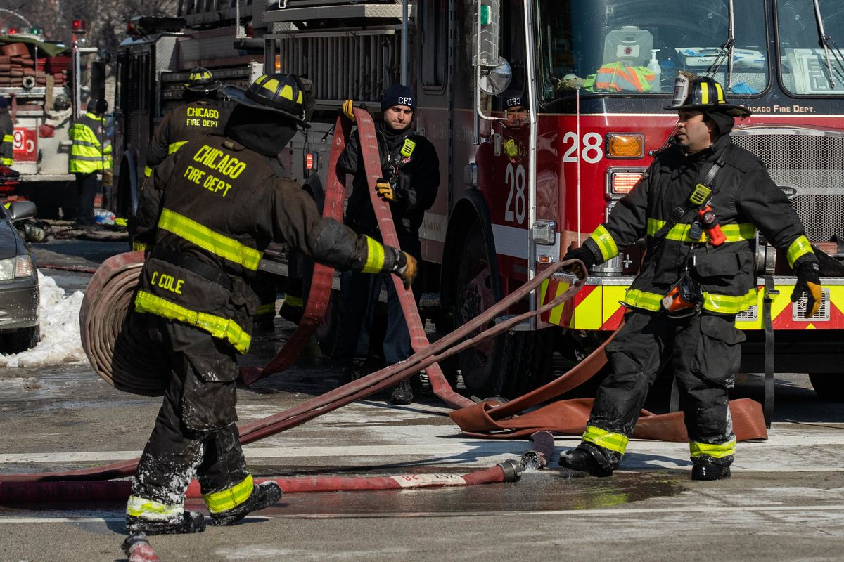 Chicago Fire Department firefighters carry a house while trying to put out an extra-alarm fire in the Bridgeport neighborhood in February.