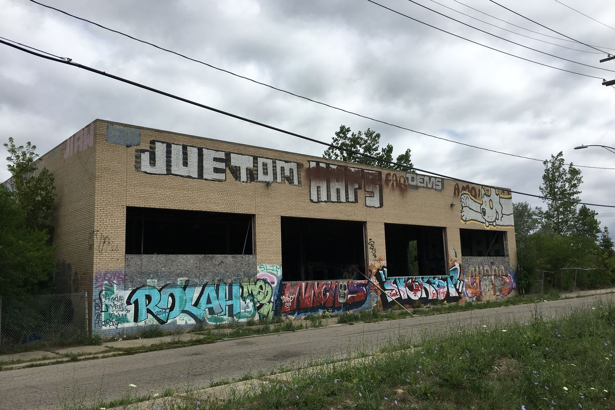 blighted building with beige stone and graffiti
