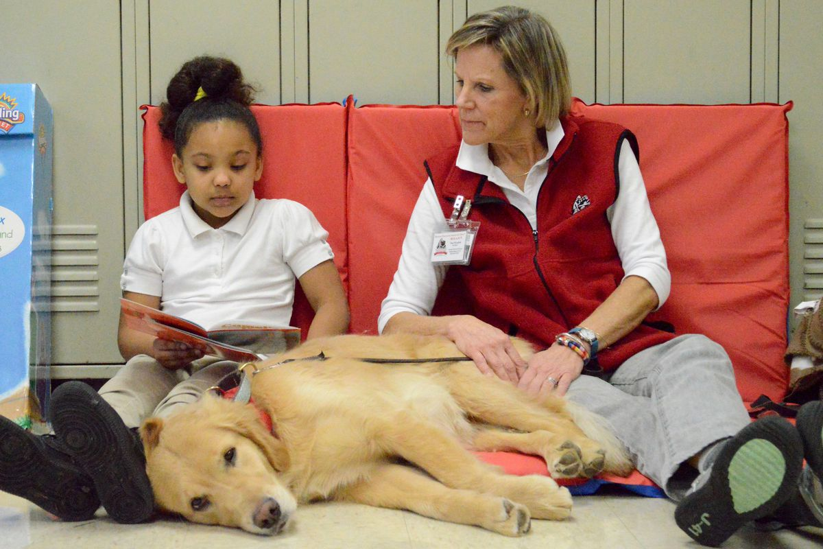 Second-grader Aaleyah Stone reads aloud to Zoe, a therapy dog who visits Keystone Elementary School with her handler, Pam Westphal.