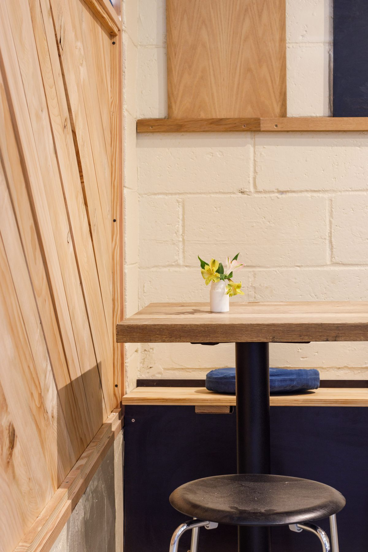 A restaurant table with a stool on one side and a wood-panelled seat on the other, the seat topped with a denim-blue cushion.