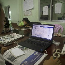 A reporter of The Voice Daily looks at its website as he and other reporters work in their newsroom at its office in Yangon, Myanmar, Monday, June 5, 2017. Police in Myanmar have arrested the newspaper's chief editor and a columnist for allegedly defaming the military by publishing an article mocking its role in the country's efforts to reach a peace agreement with fractious minority groups. A lawyer for The Voice Daily editor Kyaw Min Swe said Monday that the two were not released after being called in for questioning Friday over a lawsuit filed by the military under the country's Telecommunications Law.