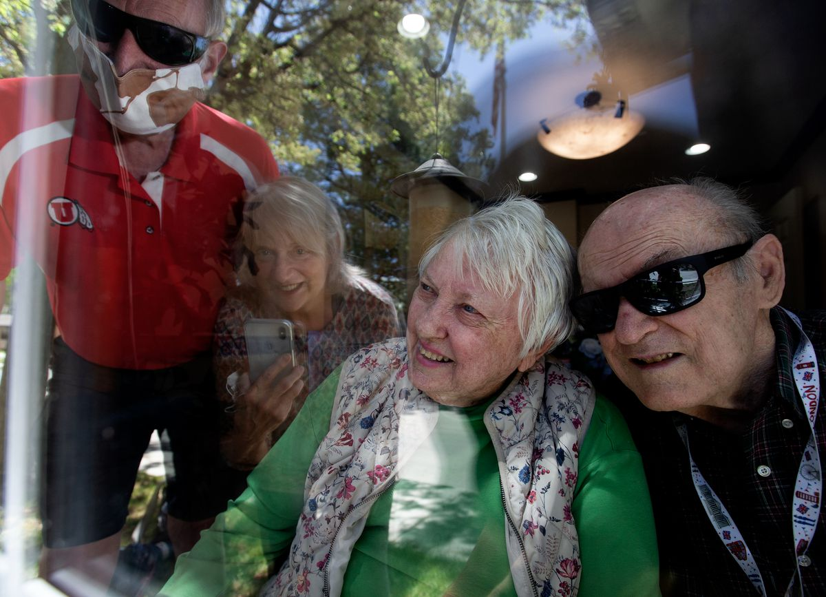 George and Nita Lutes, residents at Pacifica Senior Living in Millcreek, speak through a window with Tim and Cathy Chambless on Wednesday, April 29, 2020.