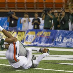 Hawaii wide receiver Marcus Kemp extends his arms out toward the end zone to score the go-ahead touchdown while being tackled by Tennessee-Martin defensive back Joseph Este late in the fourth quarter of an NCAA college football game, Saturday, Sept. 10, 2016, in Honolulu. Hawaii beat Tennessee-Martin 41-36. (AP Photo/Eugene Tanner)