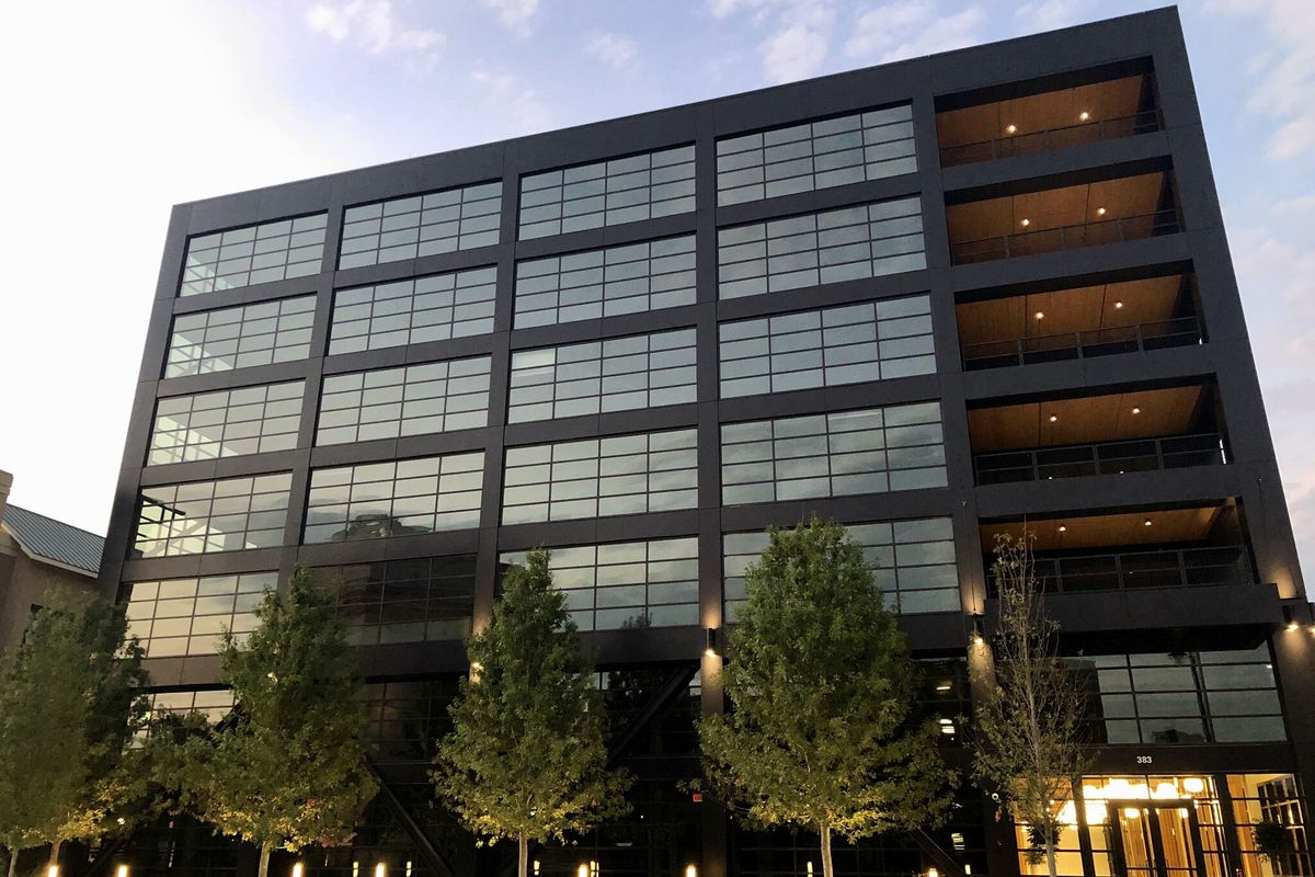 A seven-story office building with a glassy facade and outdoor patios that showcase its wooden frame.