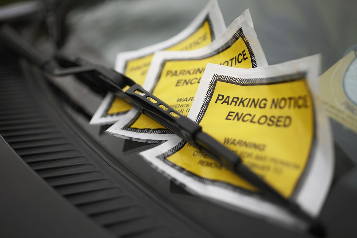 Parking tickets piled up on a windshield.