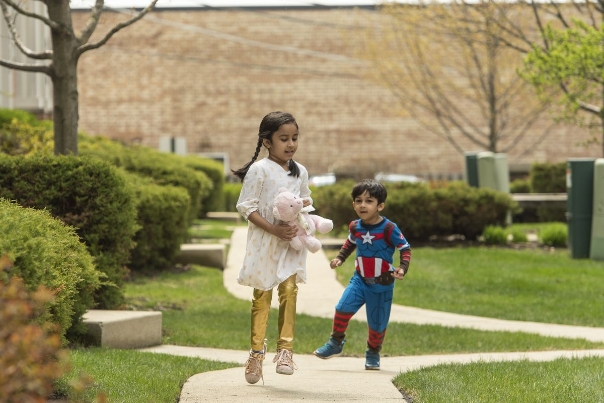 Maryam Rizvi (left) and her younger brother Idris play together in their front yard, Tuesday, April 28, 2020.
