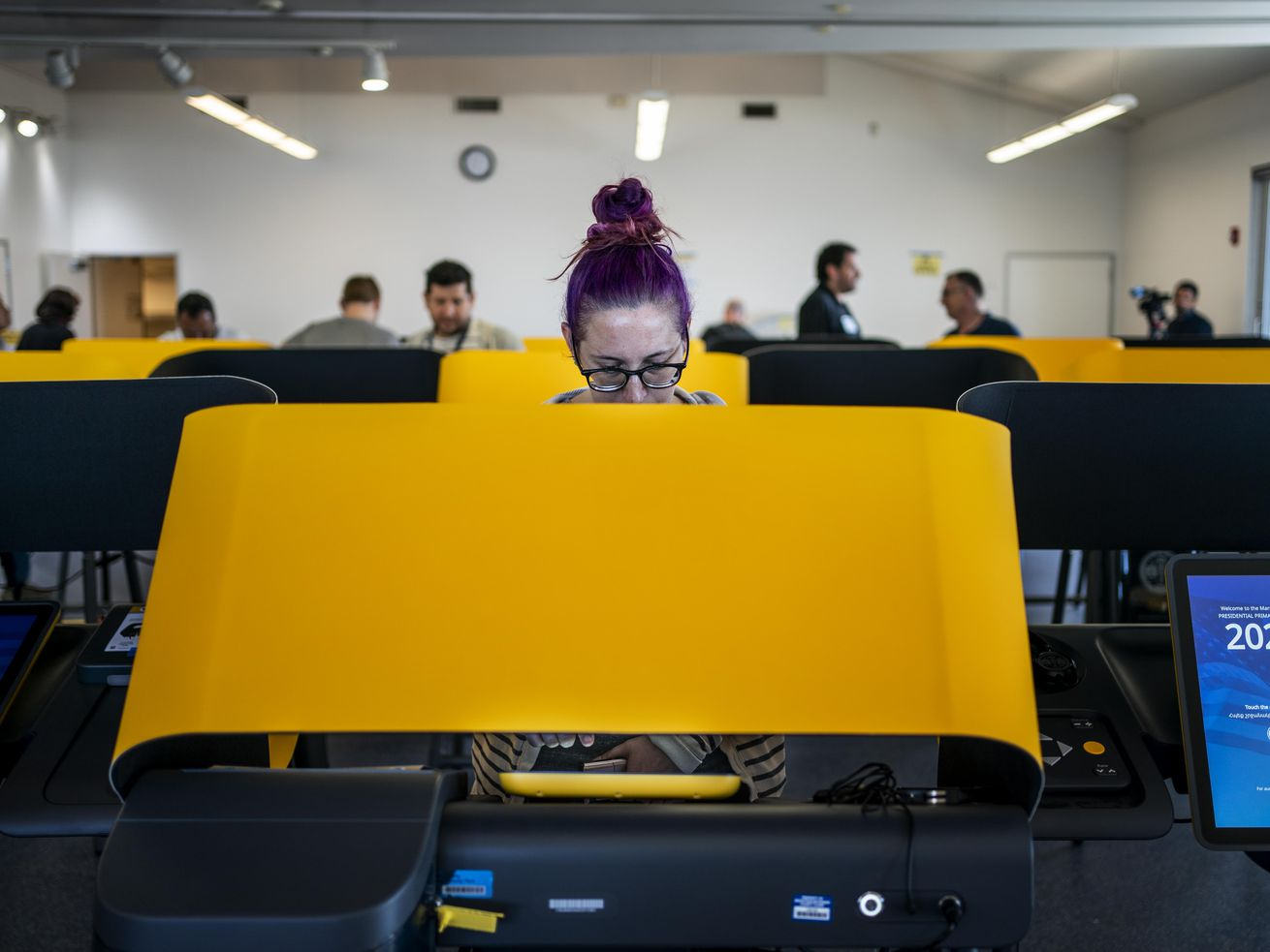 A woman behind a yellow privacy screen looks down intently as she makes her selections. behind her, people walk by in a room full of yellow booths.