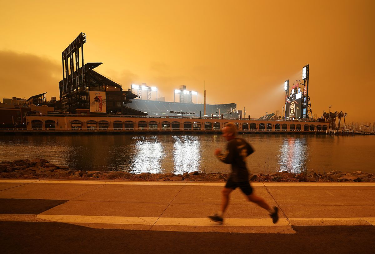 Under darkened skies from wildfire smoke, a jogger makes his way along McCovey Cove outside Oracle Park on Wednesday, Sept. 9, 2020, in San Francisco.