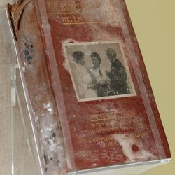 ADVANCE FOR USE SUNDAY, JULY 31, 2011 AND THEREAFTER - This Friday, June 24, 2011 photo shows a copy of Helen Keller's autobiography, a gift to Alexander Graham Bell, scorched and covered in World Trade Center dust on display in New York. Besides ending nearly 3,000 lives, destroying planes and reducing buildings to tons of rubble and ash, the Sept. 11, 2001, attacks destroyed tens of thousands of records, irreplaceable historical documents and art. (AP Photo/Mary Altaffer)