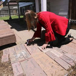 Salt Lake County Mayor Jenny Wilson signs a brick outside of a new Division of Youth Services' Milestone Program house in Sandy on Wednesday, July 8, 2020. The bricks have names of those who have impacted the house, and more bricks will be added as people come and go from the house. The four-bedroom house was remodeled in partnership with Good Shepherd Lutheran Church and will help provide housing to young adults, ages 18-21, who are experiencing homelessness.