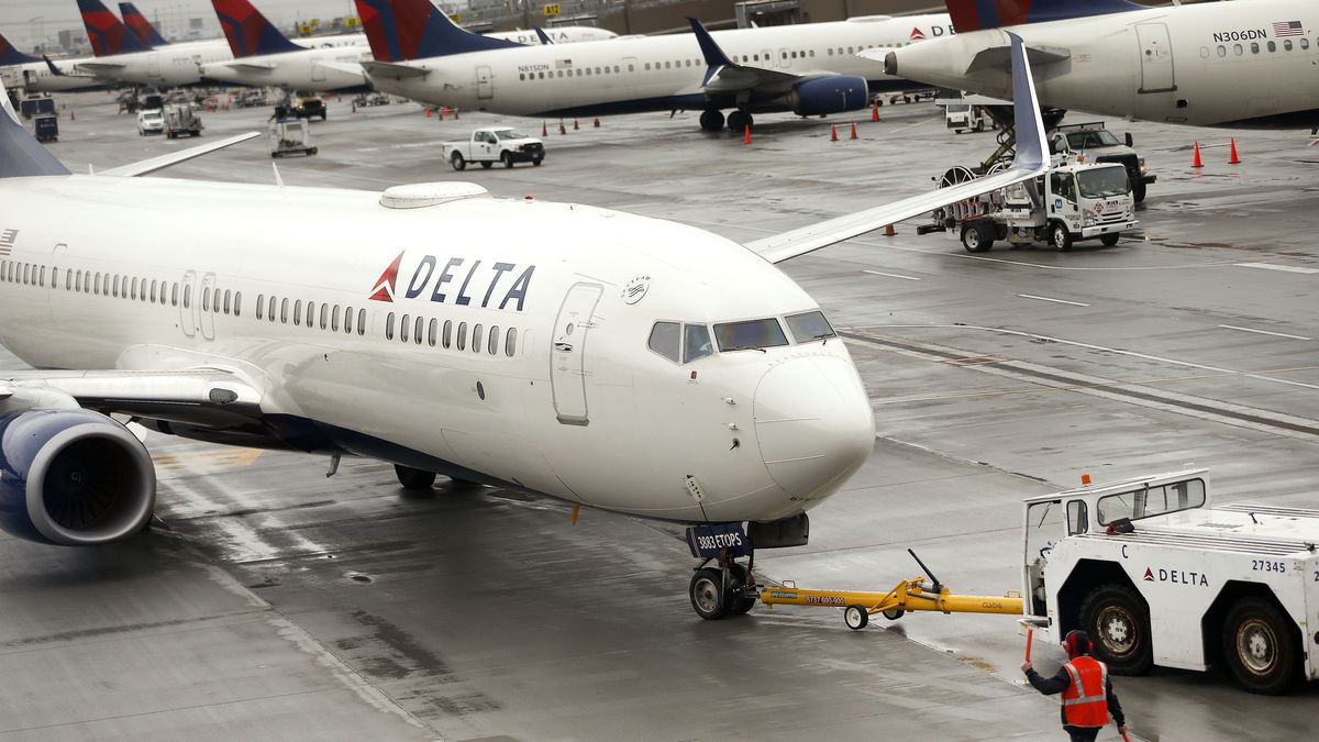 A Delta plane departs from a hangar at the Salt Lake City International Airport.