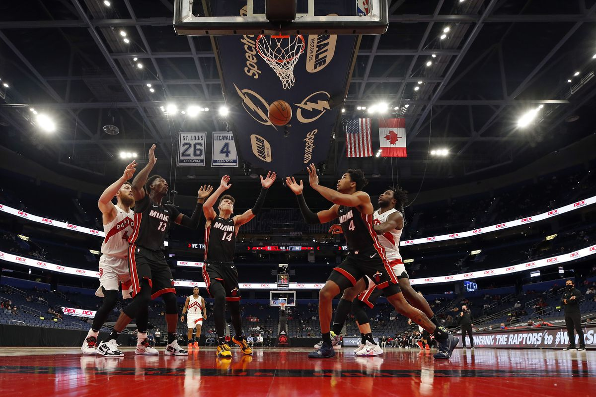 The Miami Heat and the Toronto Raptors go up for a rebound during a preseason game on December 18, 2020 at Amalie Arena in Tampa Bay, Florida.