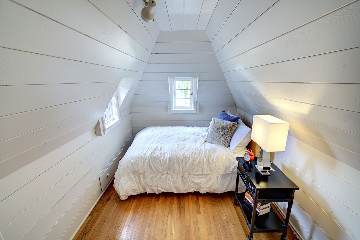 A small nook with vaulted ceilings, a bed, and a nightstand