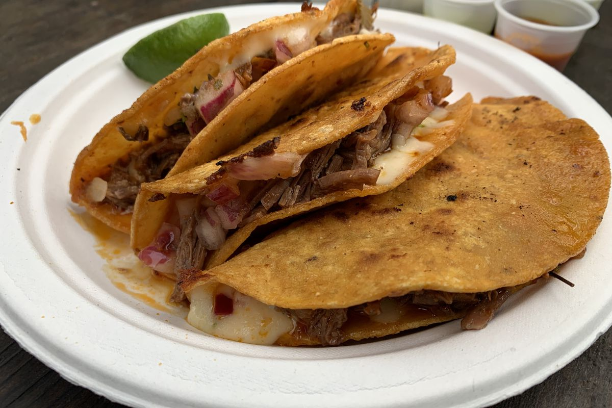 Three birria tacos on a paper plate, with a wedge of lime