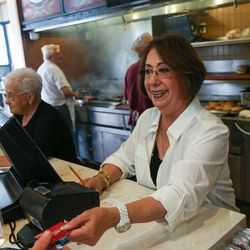 Rula Katzourakis serves customers while her husband, John, back left, tends to the broiler at Crown Burgers in Salt Lake City on Friday, Aug. 5, 2016. John and Rula Katzourakis have owned and operated Crown Burgers for 38 years.
