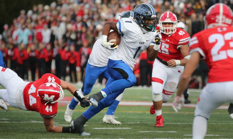 Lincoln-Way East's Jamal Johnson (1) breaks a tackle and picks up a first down against Marist.