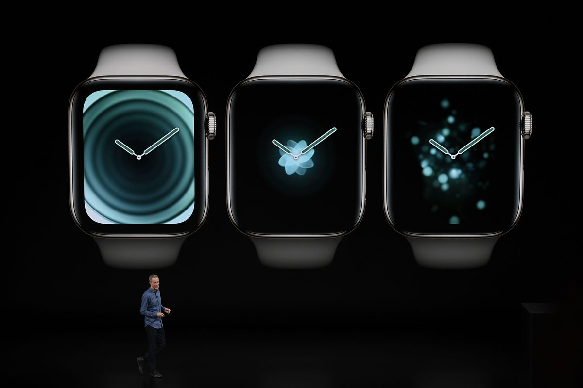 Apple COO Jeff Williams onstage in front of an image of three Apple Watches