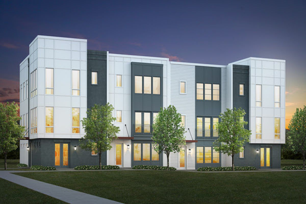 A white townhome development with trees and green grass in front.