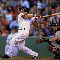 Boston Red Sox's Cody Ross hits an RBI double off a pitch by Baltimore Orioles' Luis Ayala allowing Red Sox's Dustin Pedroia to score in the eighth inning of a baseball game at Fenway Park, in Boston, Sunday, Sept. 23, 2012. The Red Sox won 2-1. Baltimore Orioles catcher Matt Wieters looks on at right.