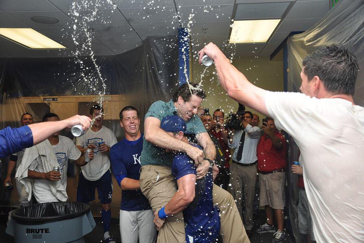 Johnny Giavotella lifts broadcaster Mark Nasser in celebration