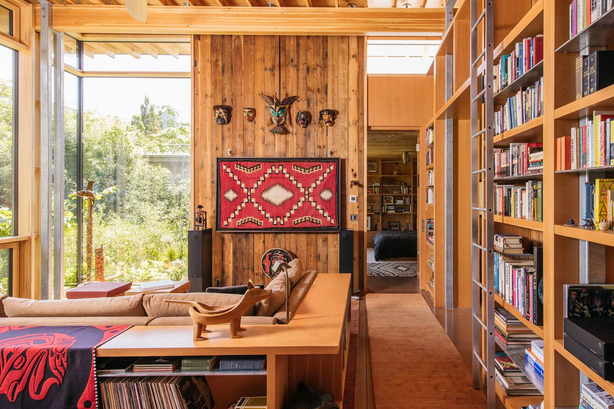 A living area.  The walls are made of wood and there are bookshelves with a ladder on one side of the room.  A large couch and several decorative works of art hang on the wall.  The windows look out onto a courtyard with lots of plants.