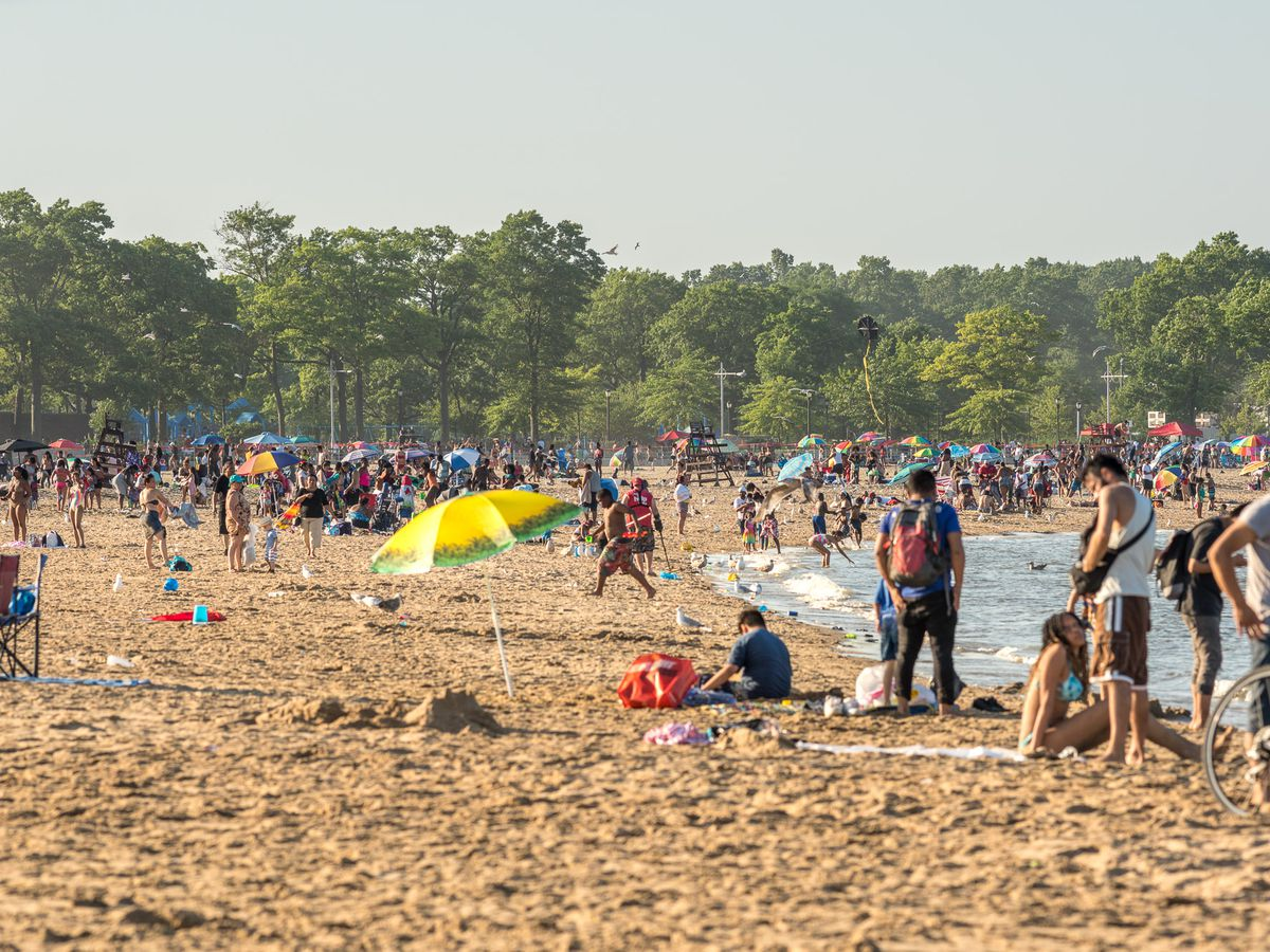 A sandy beach. There are lots of people on the beach, and a colorful beach umbrella.