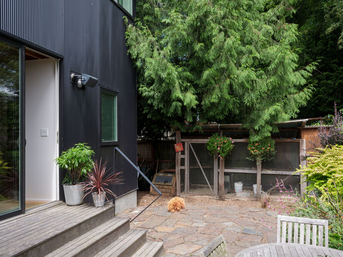 A house with a black metal facade is adjacent to a yard with an outdoor patio area with a table and chairs. There is a chicken coop and various wildflowers in the yard.