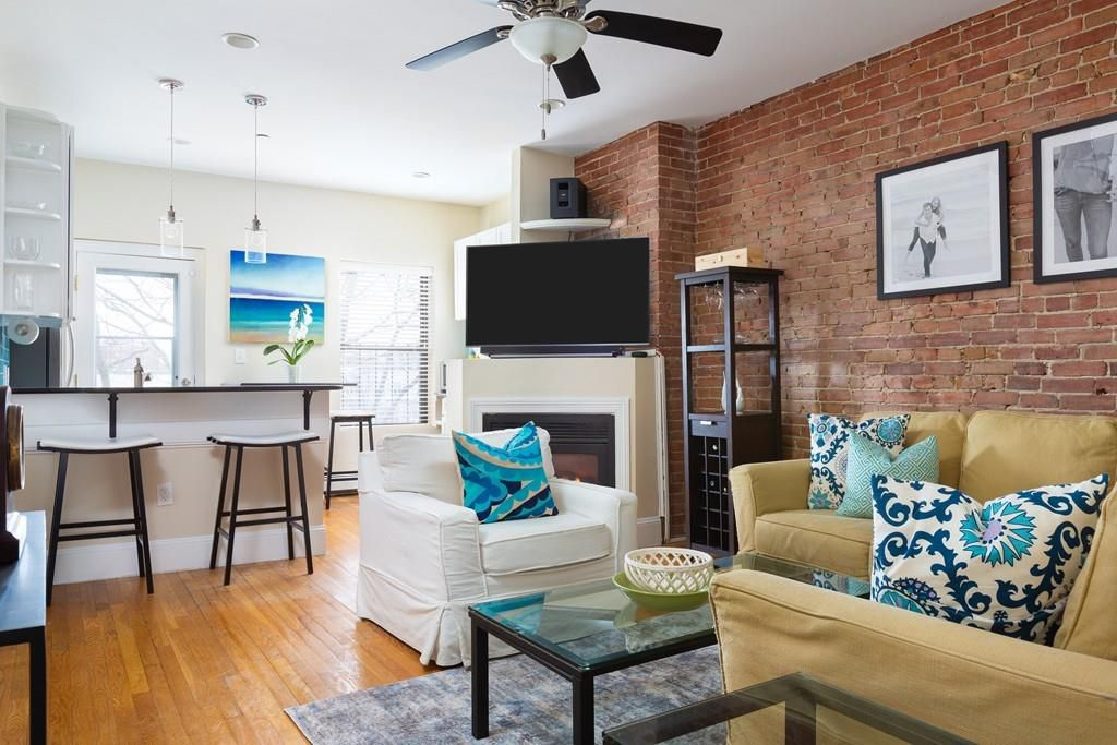A snug living room with furniture and a ceiling fan.