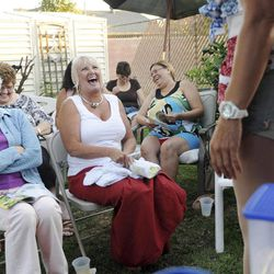 This Friday, Aug. 5, 2011 photo shows Susanne Cameron, left, and Barbara Cassidy, right, as they laugh with others while being entertained by Kevin Farrell dressed as Dee W. Ieye during a Tupperware party in Bellflower, Calif. Tupperware, it seems, is enjoying a renaissance 65 years after it first hit the market with Wonder Bowls, Bell Tumblers and Ice-Tup molds for homemade frozen treats.