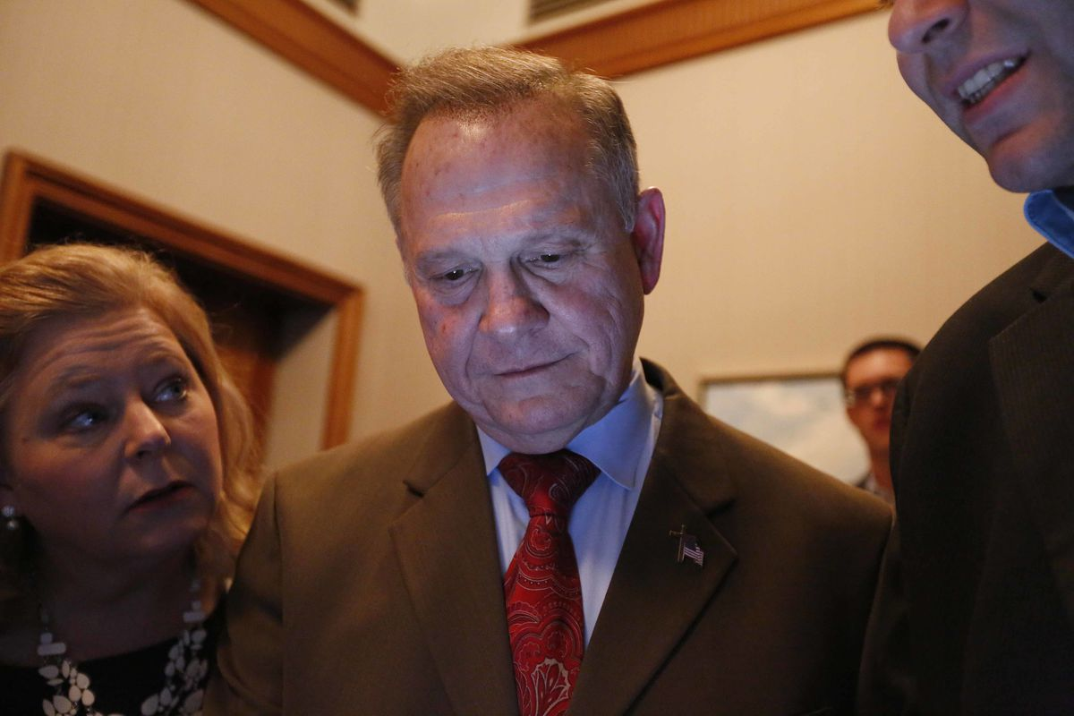Republican U.S. Senate candidate Roy Moore, center, looks at election returns with staff during an election-night watch party at the RSA activity center, Tuesday, Dec. 12, 2017, in Montgomery, Ala. (AP Photo/Brynn Anderson)