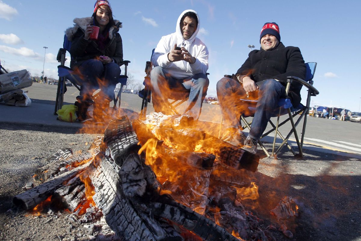 Fans warm up with a pre-game fire
