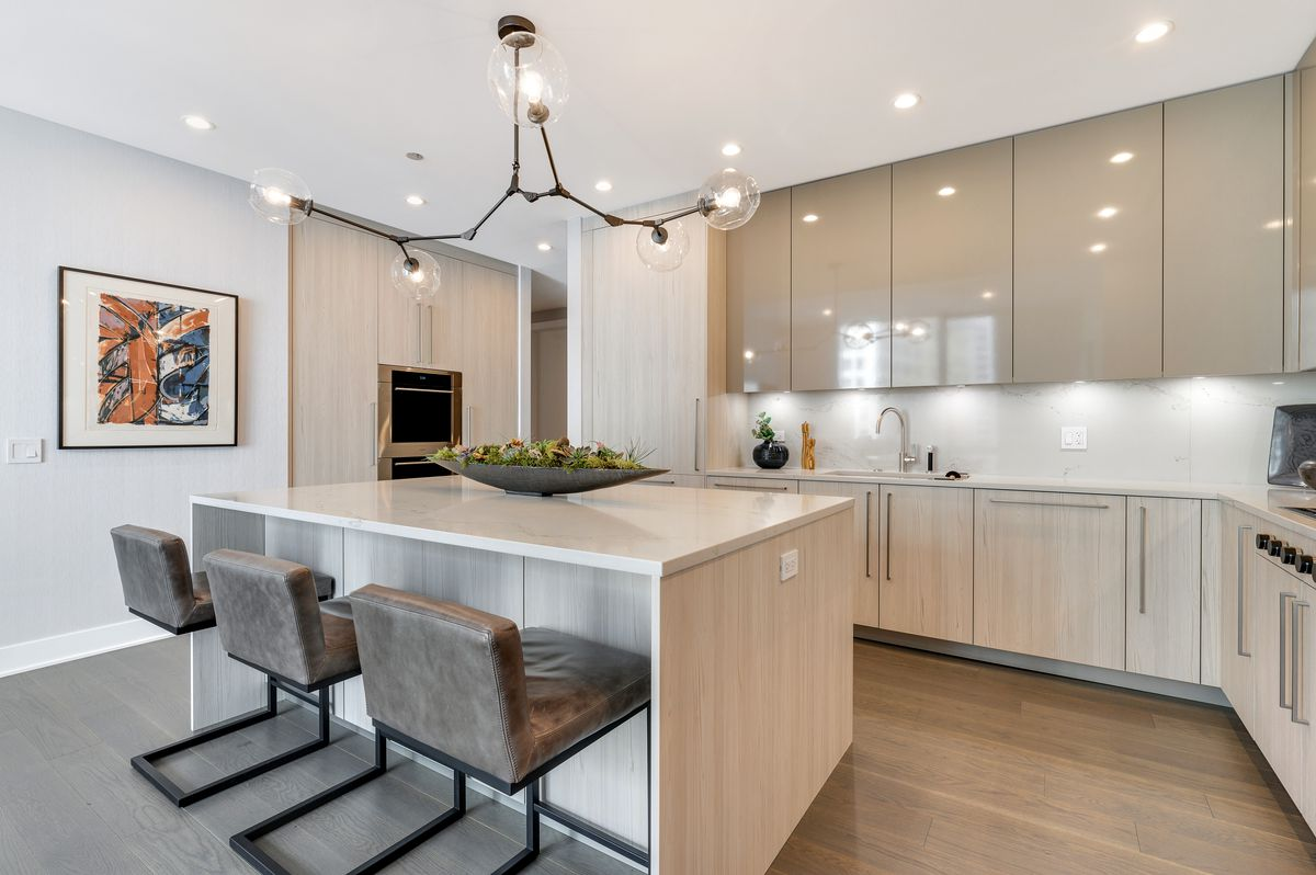 A contemporary kitchen with sleek cabinets, stone counters, three leather-backed stools, and a light fixture with multiple glass globes.