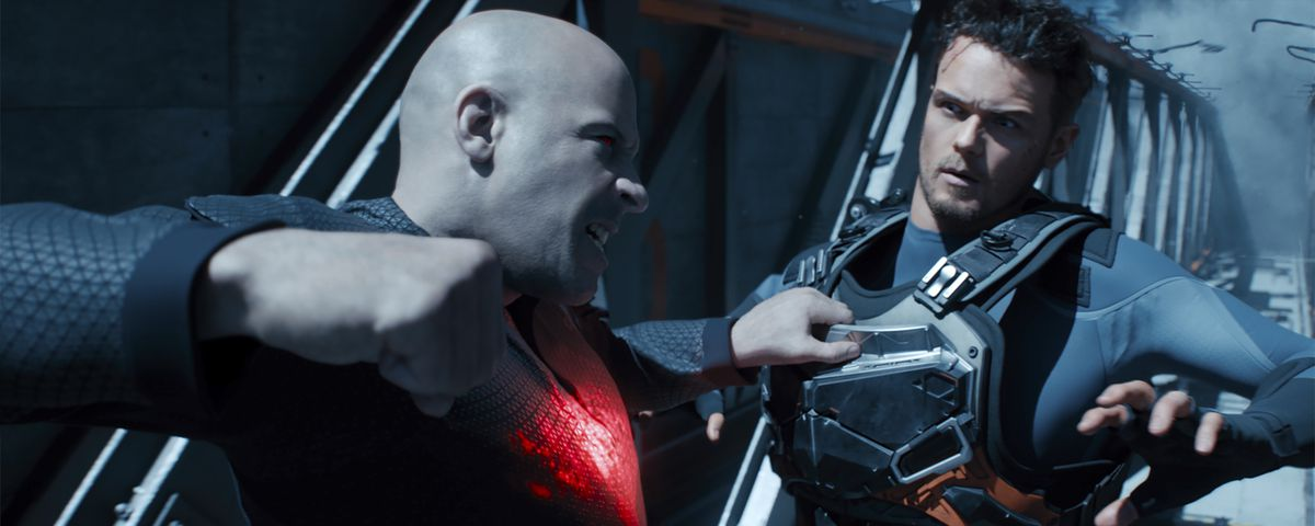A snarling Vin Diesel, with glowing red eyes and a glowing red patch in his chest, grabs a fellow soldier and pulls his fist back for a punch in Bloodshot.