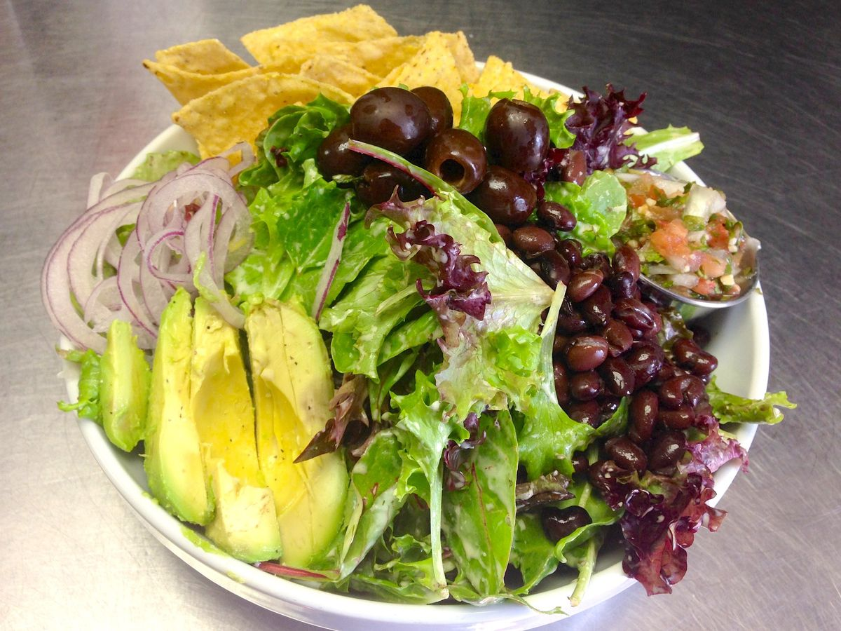 Salad with avocado, black olives, and tortilla chips.