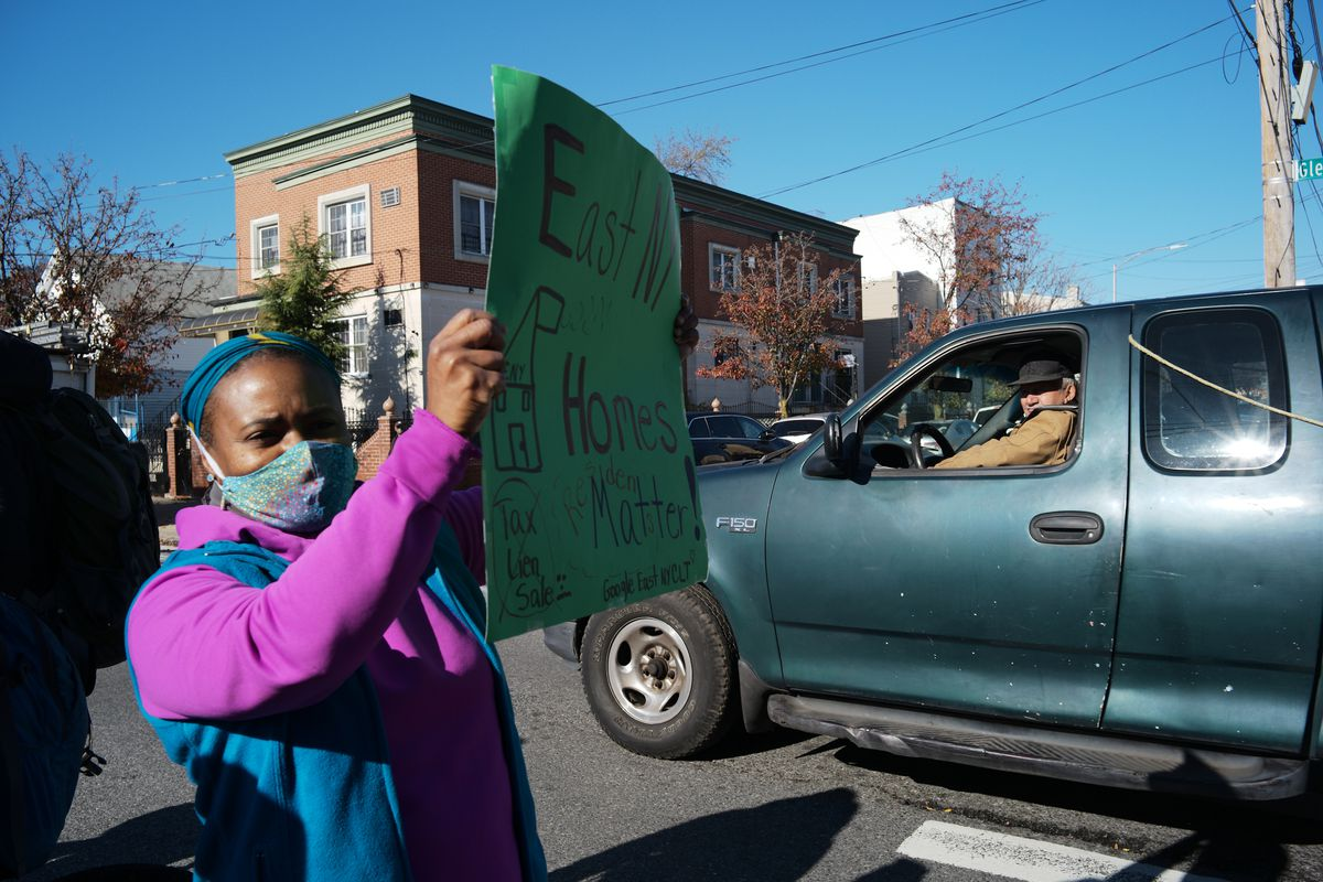 A protester in East New York holds up a sign calling for an end to lien sales.