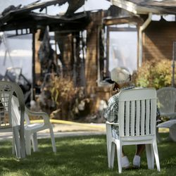 The owner of two homes damaged in a structure fire watches firefighters work at the scene of a house fire in Millcreek on Thursday, July 9, 2020. The fire is the third structure fire on this block in a week, and the second fire at the same house. Four houses in total have been damaged in the week's fires.
