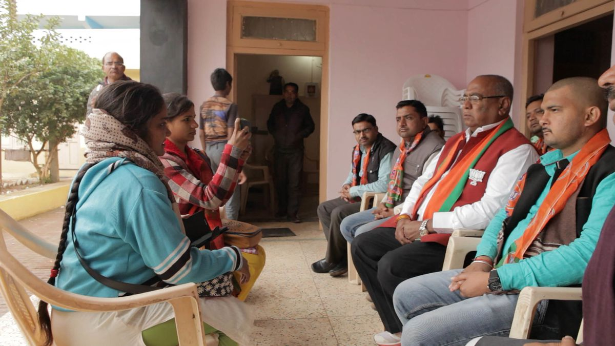 In India, two women journalists sit across from a row of politicians and operatives, interviewing them.