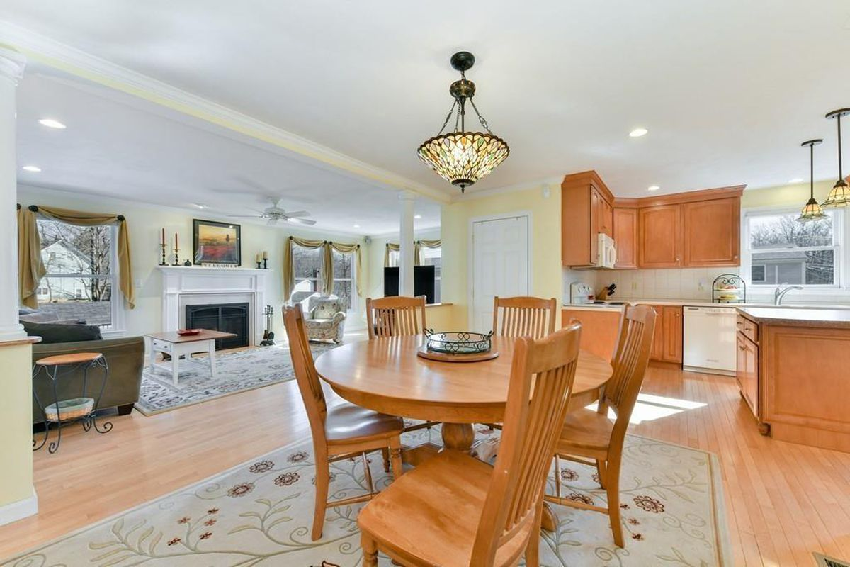 An open dining room-living room-kitchen area on the first floor of a large house.