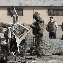 A French soldier investigates the scene of a suicide bombing in Kabul, Afghanistan, Tuesday, Sept. 18, 2012. A suicide bomber rammed a car packed with explosives into a mini-bus carrying foreign aviation workers to the airport in the Afghan capital early Tuesday, killing at least nine people in an attack a militant group said was revenge for an anti-Islam film that ridicules the Prophet Muhammad.