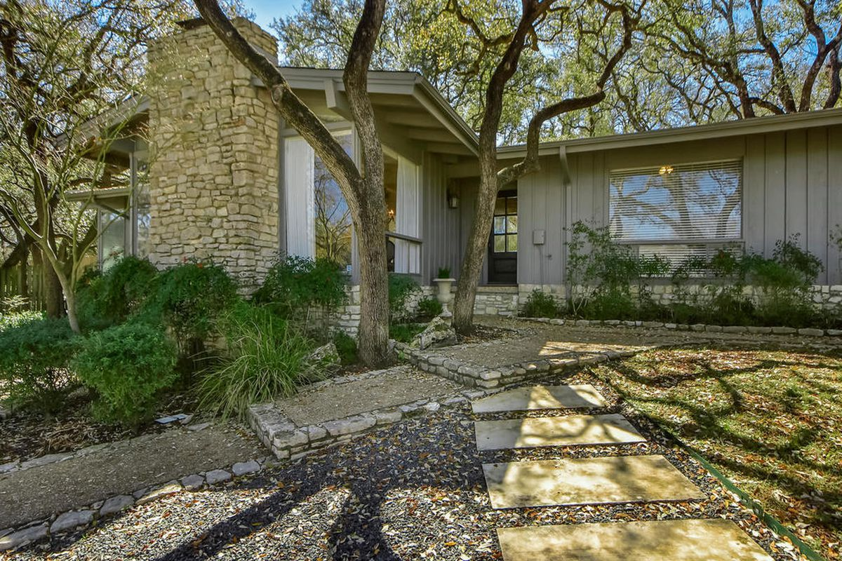 Entrance of 1960s ranch-style house with stepping stones, large tree, gray walls and big stone chimney