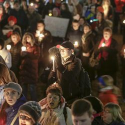 """Participants sing """"This Land is Your Land"""", during a multi-faith candle light vigil in support of refugees and immigrants, held Tuesday, Jan. 31, 2017, in Omaha, Neb."""